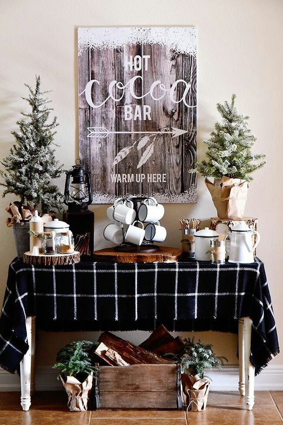 a rustic hot cocoa bar with small Christmas trees, a snowy sign and a windowpane printed tablecloth