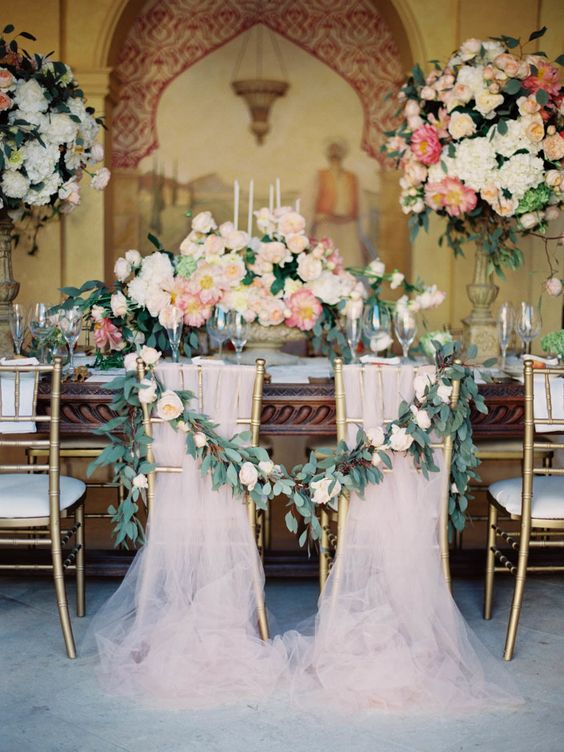 blush tulle covering the chairs in layers and a greenery and bloom garland to tie the sweetheart chairs and make them stand out