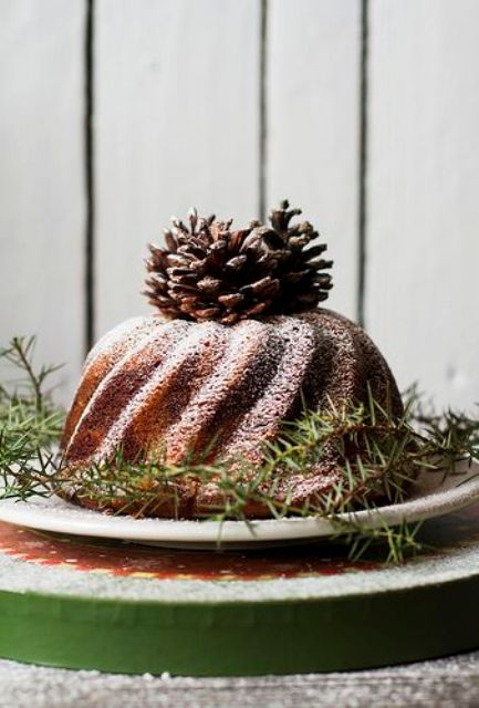 a bundt cake topped with pinecones and evergreens is a great idea to make your dessert table variable