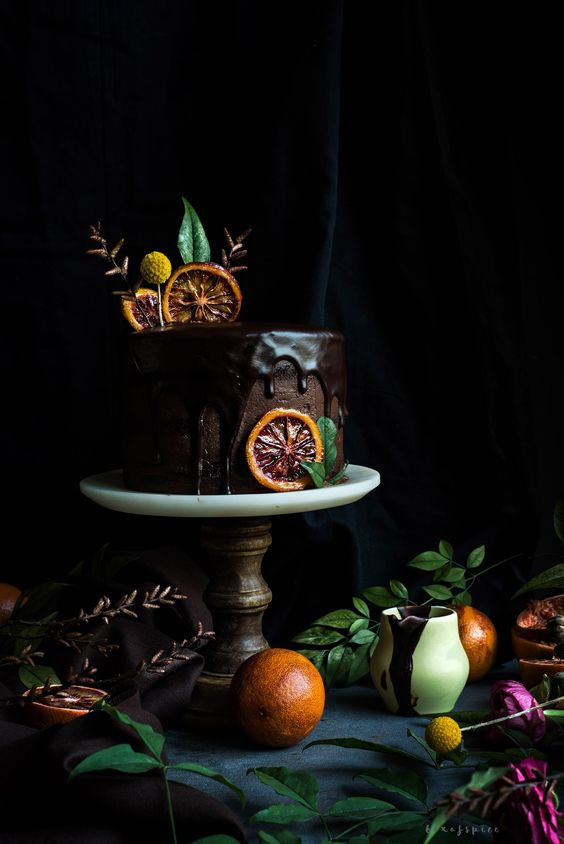 a chocolate wedding cake with chocolate dripping, bloody orange slices on top and an orange slice on the side