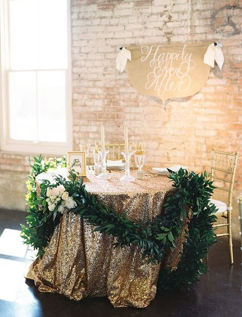 a gold glitter tablecloth and a greenery garland with blooms for highlighting a sweetheart table