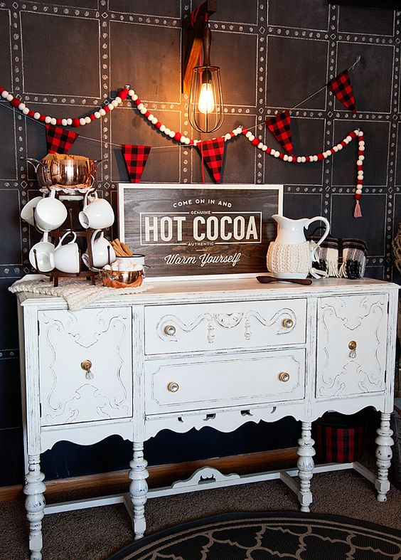 a gorgeous hot cocoa bar of a vintage sideboard, a plaid banner and mugs with knit cozies