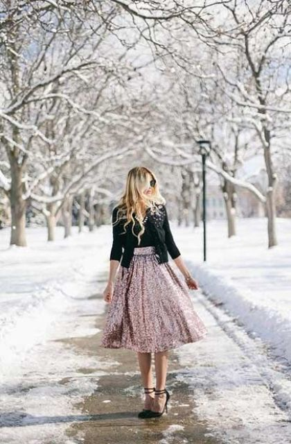 a pink sequin midi skirt, a black top, a black crop jacket with embellishments and black shoes