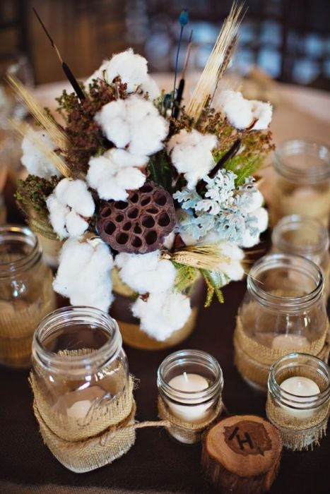a rustic centerpiece with pale miller, wheat, cotton and greenery for a fall or winter wedding