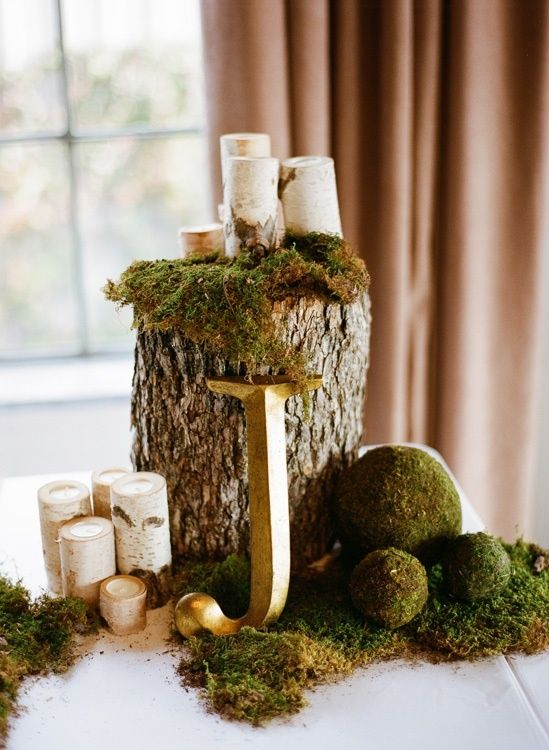 a woodland wedding centerpiece with a tree stump, moss balls and birch candle holders