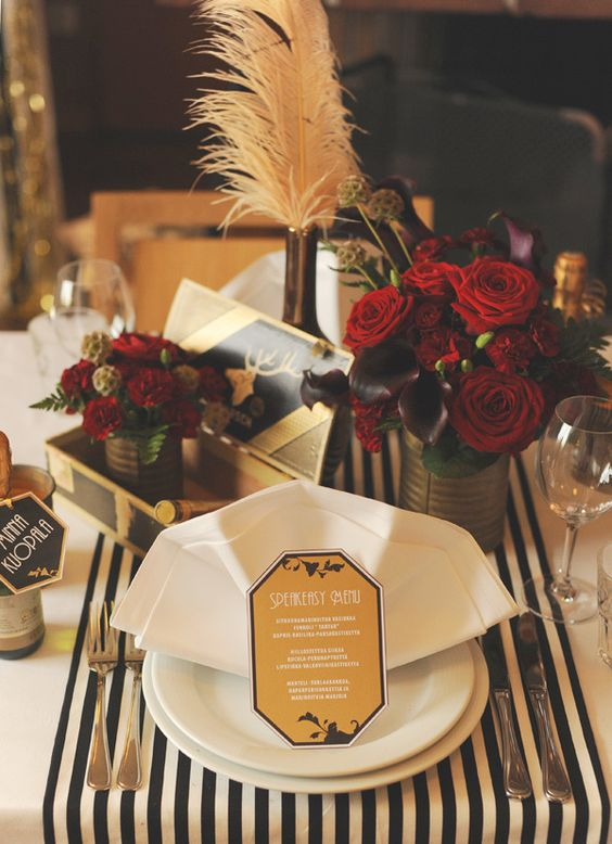 a chic tablescape with red roses, deep purple callas, feathers and a striped table runner