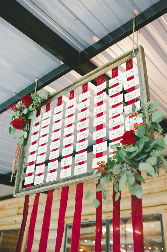 a cool framed seating chart with red ribbons, cards and lush greenery and red roses