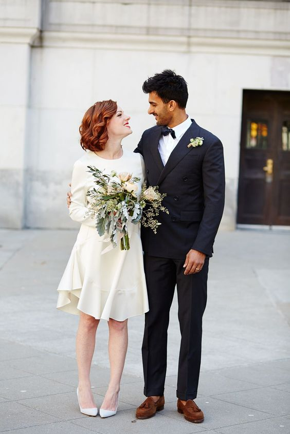 a modern wedding dress with a high neckline, long sleeves and an asymmetrical skirt with white shoes