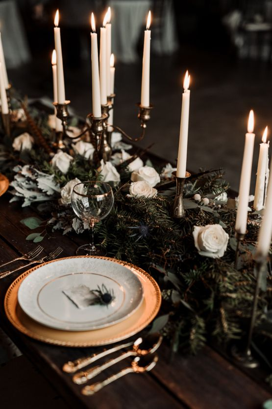 a moody winter tablescape with an evergreen garland with white roses and thistles, candles and feathers