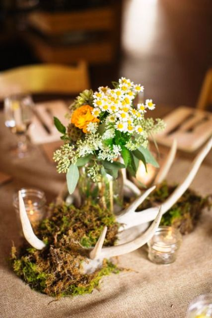 a woodland wedding centerpiece with moss, antlers and yellow blooms is great for the fall