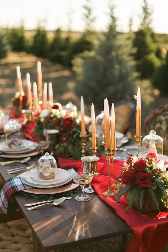 an elegant tablescape with red roses, plaid napkins, gold candle holders and a red silk table runner