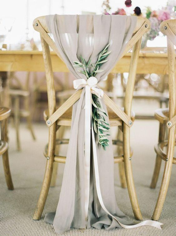 dove grey airy fabric, a white ribbon and an olive branch to decorate chairs, ideal for a wedding in Italy