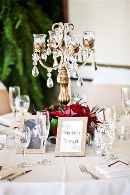 a creative centerpice of a gilded and crystal candelabra and red blooms at its base