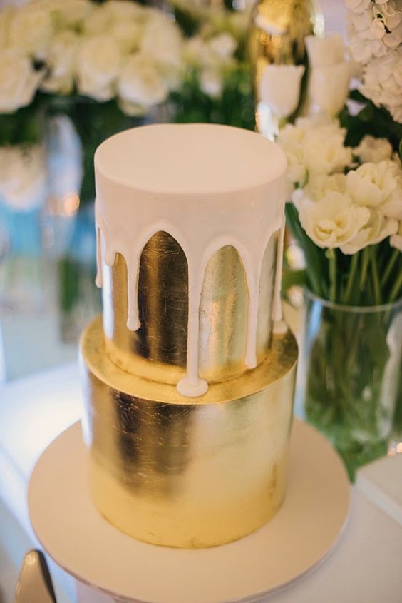 a gold metallic wedding cake with white chocolate dripping for a trendy glam winter wedding