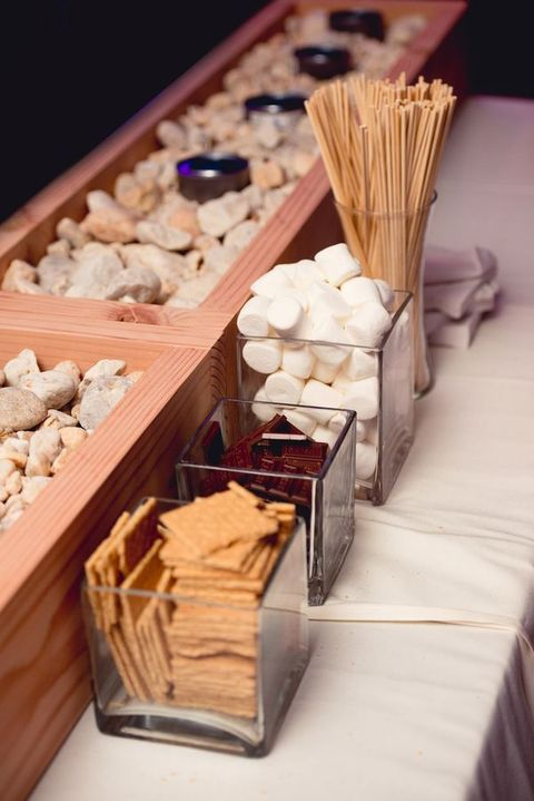 a rustic bar with wood boxes and pebbles for making s'mores looks cute and chic