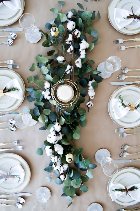 a table runner of eucalyptus and cotton with candles is great for any fall or winter wedding