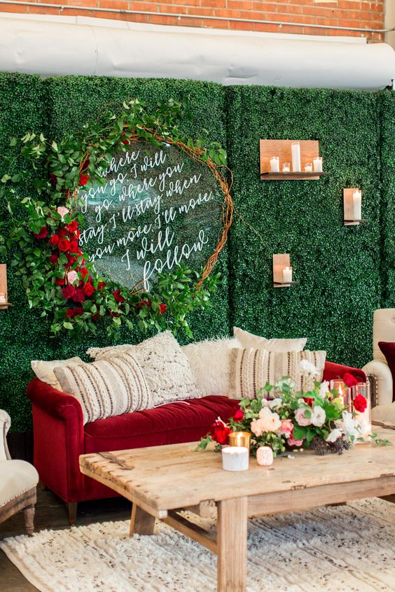 a wedding lounge with a greenery wall, lush greenery and red roses and a red velvet sofa