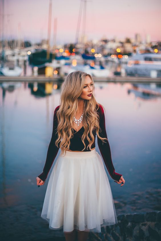 a white tulle skirt, a burgundy velvet crop top with long sleeves and a statement necklace