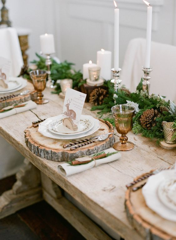 an elegant rustic table setting with an evergreen and pinecone garland, candles, wood slices and cinnamon sticks