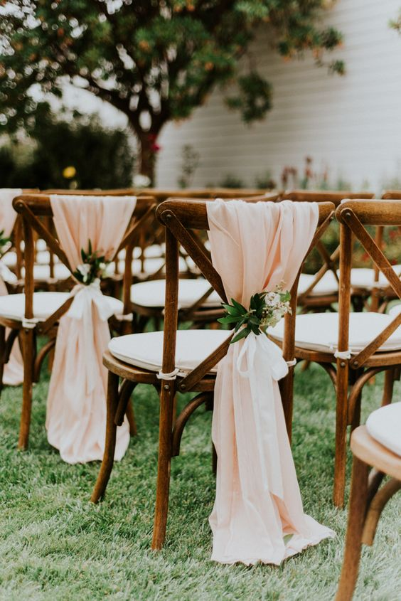 farmhouse chairs with peachy fabric, greenery and bloom posies for a soft look are ideal for spring
