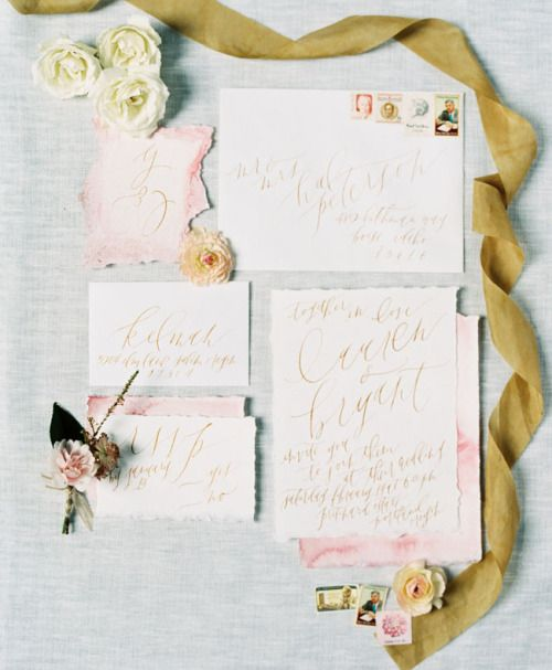 pastel pink wedding invitation set with a raw edge, gold calligraphy and some flowers