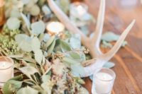 21 wedding table decor with lush greenery, candles and antlers is a great idea for a rustic wedding