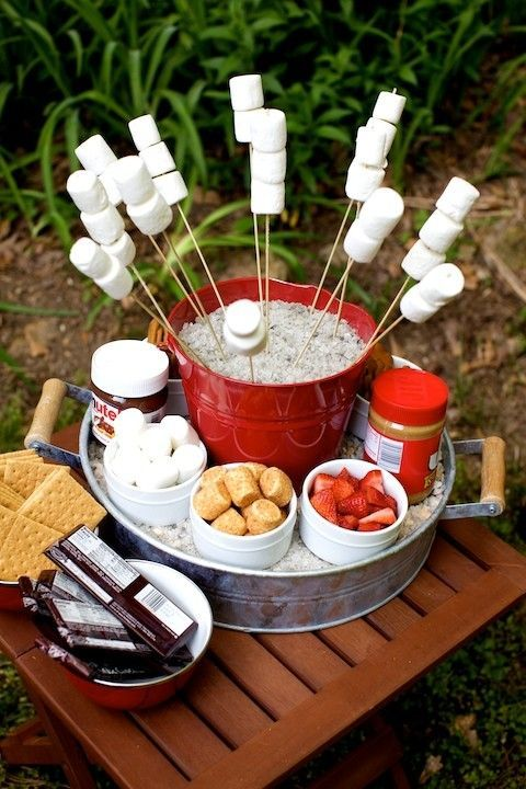 a cute small s'mores bar with marshmallows arranged on sticks and with various sweets