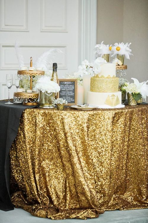 a glam dessert table with a gold sequin tablecloth, gold stands and a white and gold wedding cake