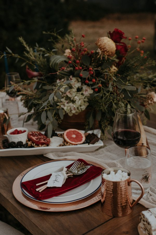 a moody tablescape with dark florals, velvet napkins and hot chocolate in copper mugs