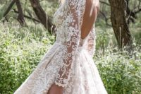 22 a 'nude' lace high low wedding gown with long sleeves, a bateau neckline and an open back