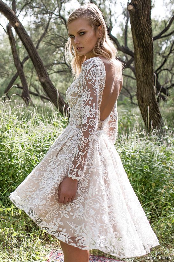 a 'nude' lace high low wedding gown with long sleeves, a bateau neckline and an open back