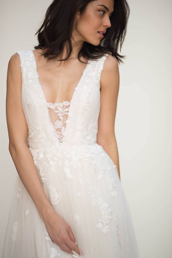 a romantic floral applique wedding dress with an illusion plunging neckline for a romantic bride