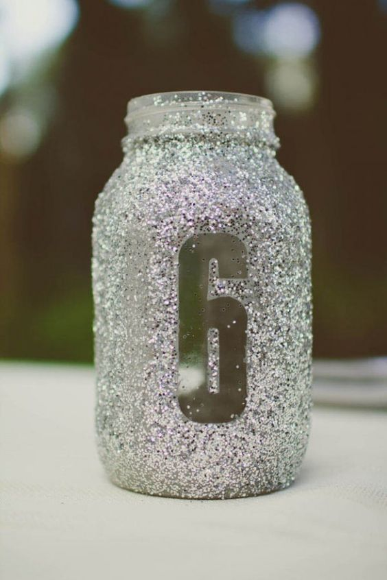 a silver glitter mason jar with a table number doubles as a candle lantern