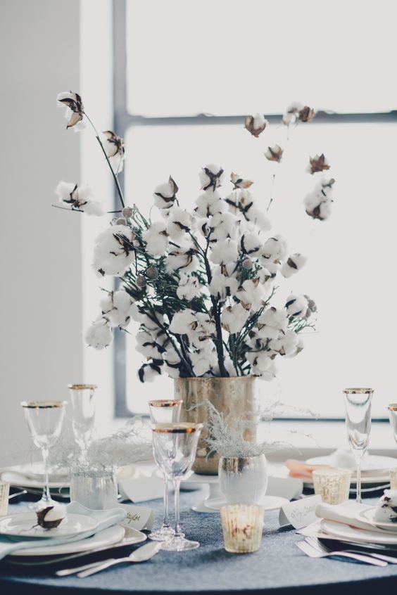 a wedding centerpiece of a brass vase and cotton branches looks wow and cute for winter