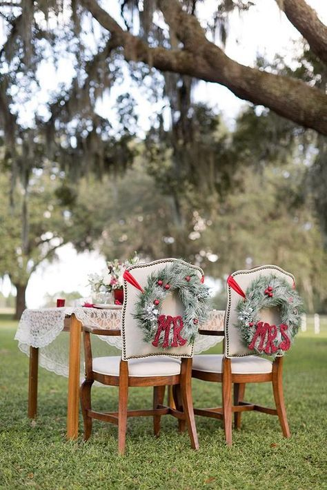 evergreen wreaths with red ornaments and red ribbons on the chairs for decor