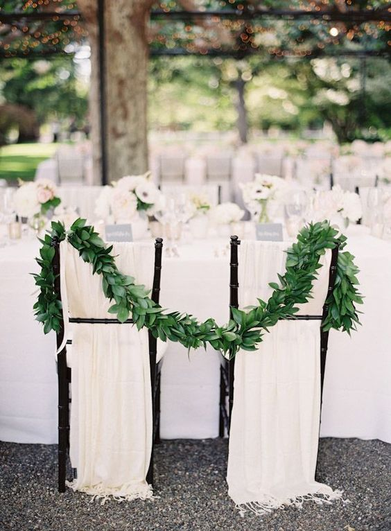 ivory fabric and a lush foliage garland to make the sweetheart chairs stand out and look inspiring