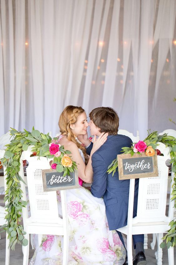 simple rustic chalkboard signs, lush greenery and bold blooms for wedding chair decor