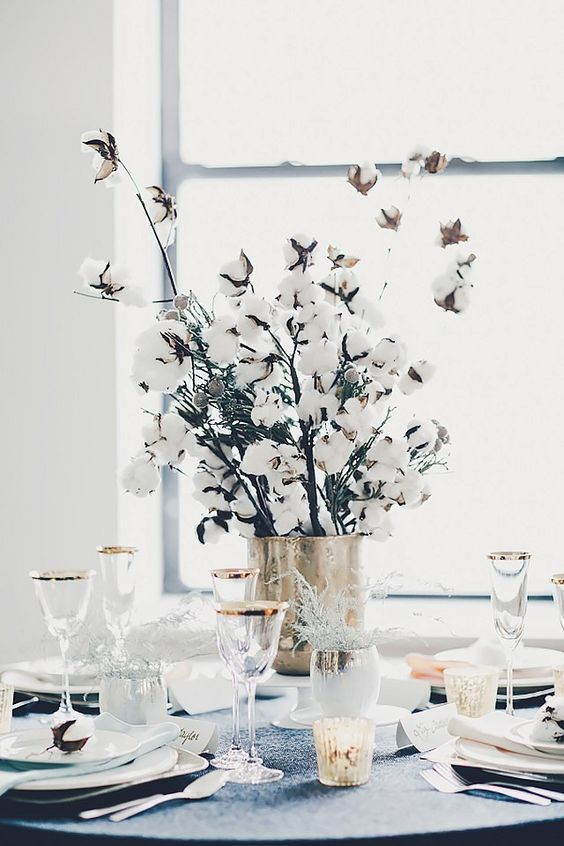 a gilded vase with cotton branches is a chic idea to add coziness to your winter wedding