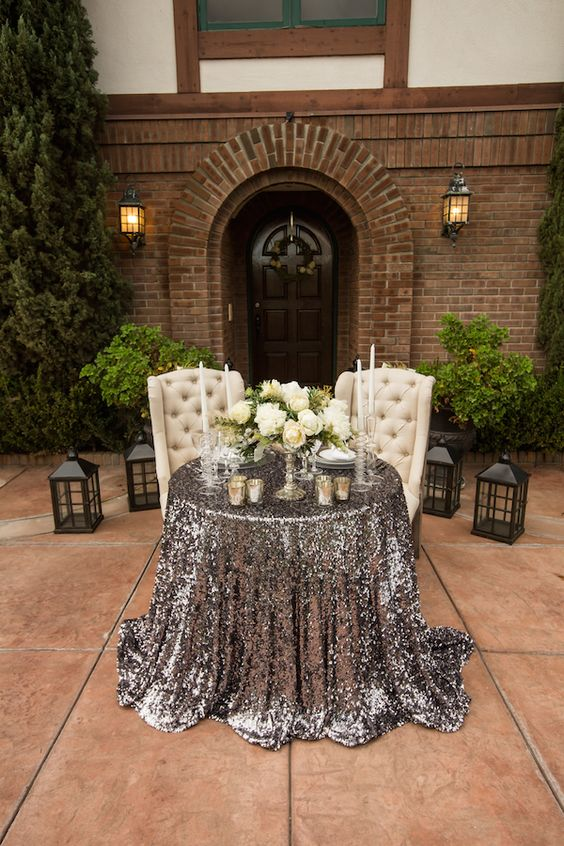 a glam sweetheart table with white upholstered chairs, a silver sequin tablecloth, white blooms and candles