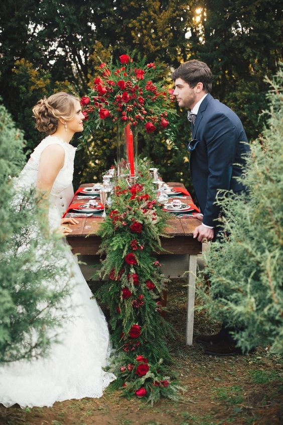 a lush evergreen table runner with red roses is right what you need for a wedding tablescape