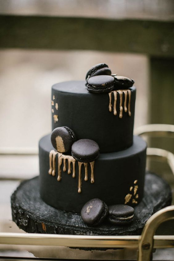 a matte black wedding cake with gold dripping, gold leaf and macarons on top for a moody wedding