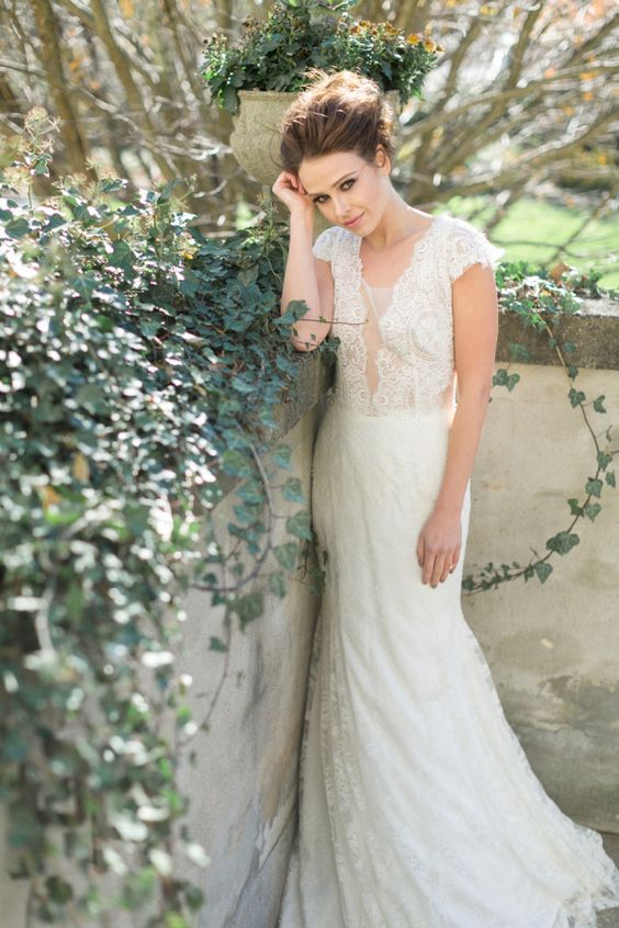 a romantic lace wedding dress with cap sleeves and an illusion plunging neckline looks very sweet