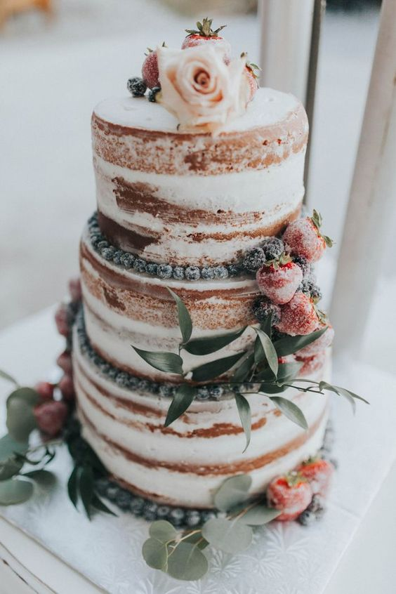 a semi naked wedding cake topped with sugared berries, foliage and a blush rose