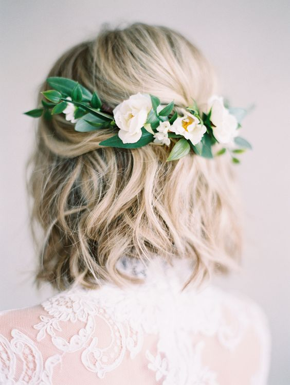 a wavy hairstyle with fresh white blooms and greenery on the back for a romantic bride