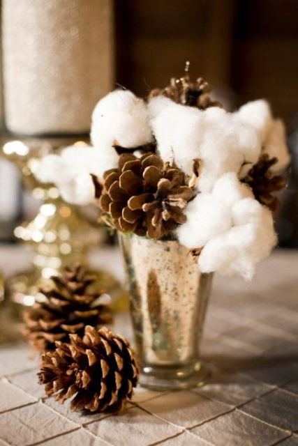 a wedding centerpiece with a metallic vase with cotton and pinecones for a winter wedding