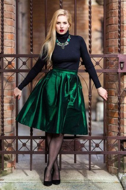 an emerald knee skirt, a black turtleneck, a statement necklace, black suede shoes and black tights