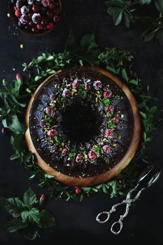 an ultimate chocolate bundt cake with sugared cranberries, pistachios and int leaves