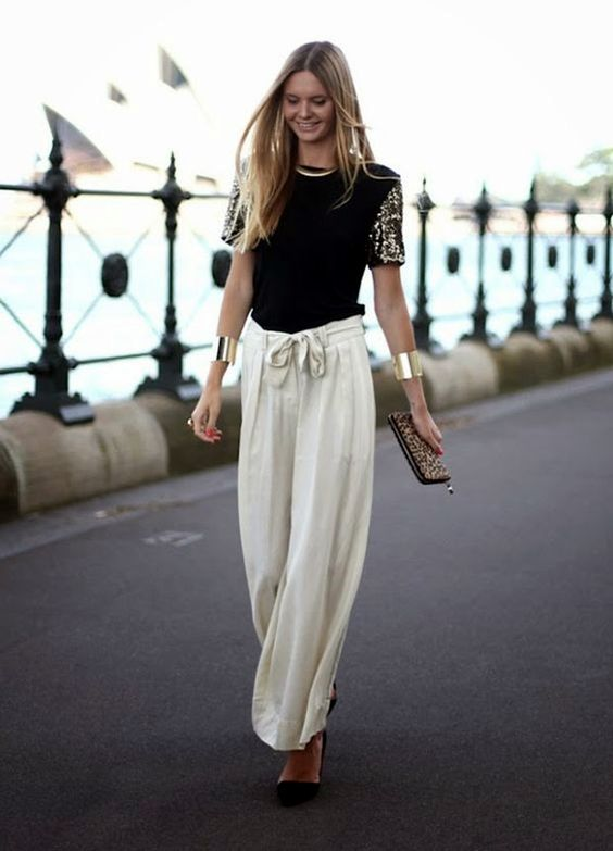 a black shirt with embellished sleeves, neutral flowy pants, a statement necklace, black suede shoes and a leopard print clutch