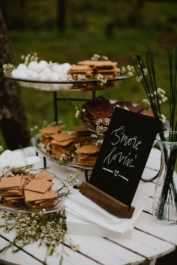 a cute rustic s'mores bar decorated with flowers and chalkboard signs for a rustic wedding