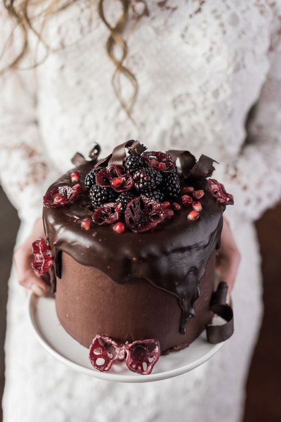 a delicious moody wedding cake with chocolate dripping, berries and pomegranate
